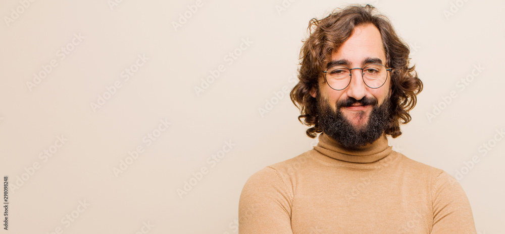 Fototapeta young bearded crazy man smiling positively and confidently, looking satisfied, friendly and happy against flat color wall