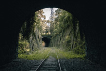 View Of Old Abandoned Train Tracks Overgrown With Grass Through Dark Railroad Tunnel