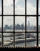 View Through Aged Window On Warehouse And Brooklyn Bridge Across East River In Sunlight
