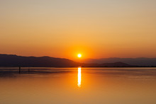 Orange Sun Going Down Behind Dark Hills Reflecting In Peaceful Slightly Rippled Water Creating Romantic Seascape