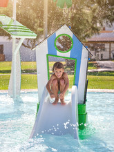 Happy Shirtless Boy Smiling And Sitting On Haunches On Small Slide While Having Fun In Water Park On Sunny Day