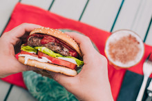 Anonymous Hands Holding A Delicious Homemade Cheeseburger With Lettuce, Tomato And Sauces