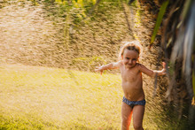Full Body Shirtless Little Girl In Panties Playing Under Drops Of Clean Water While Having Fun On Lawn In Yard On Sunny Summer Day