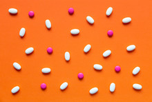 Various Pink And White Pills On A Bright Orange Background
