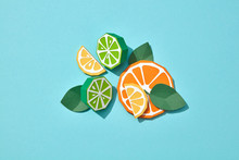 Handcraft Paper Composition Of Different Pieces Of Citrus Fruits Lime, Lemon, Orange With Mint Leaves On A Blue Background With Copy Space. Flat Lay