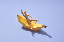 A Miniature Wooden Doll On A Paper Handcraft Banana Presented On A Purple Background With Copy Space. Nutrition Concept