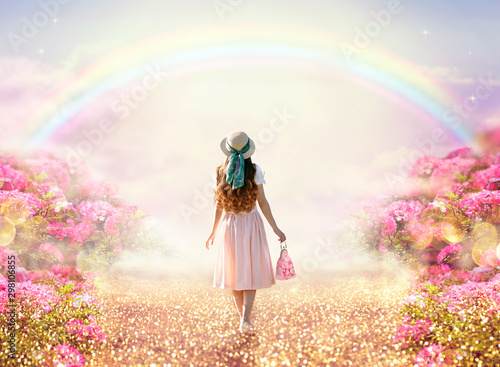 Fototapeta Young lady woman in romantic pink dress, retro hat, bag walking along rose garden path leading to fabulous rainbow unicorn house, flecks of sunlight on road. Tranquil fantasy scene, fairytale hills. obraz