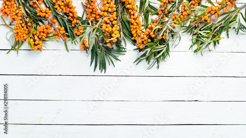 Photo  Buckthorn berries on a branch on a white background Wooden