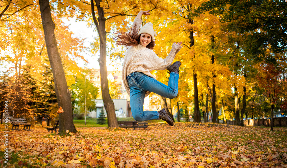 Fototapeta Happy young woman jumping with raised arms on colorful autumn leaves city background