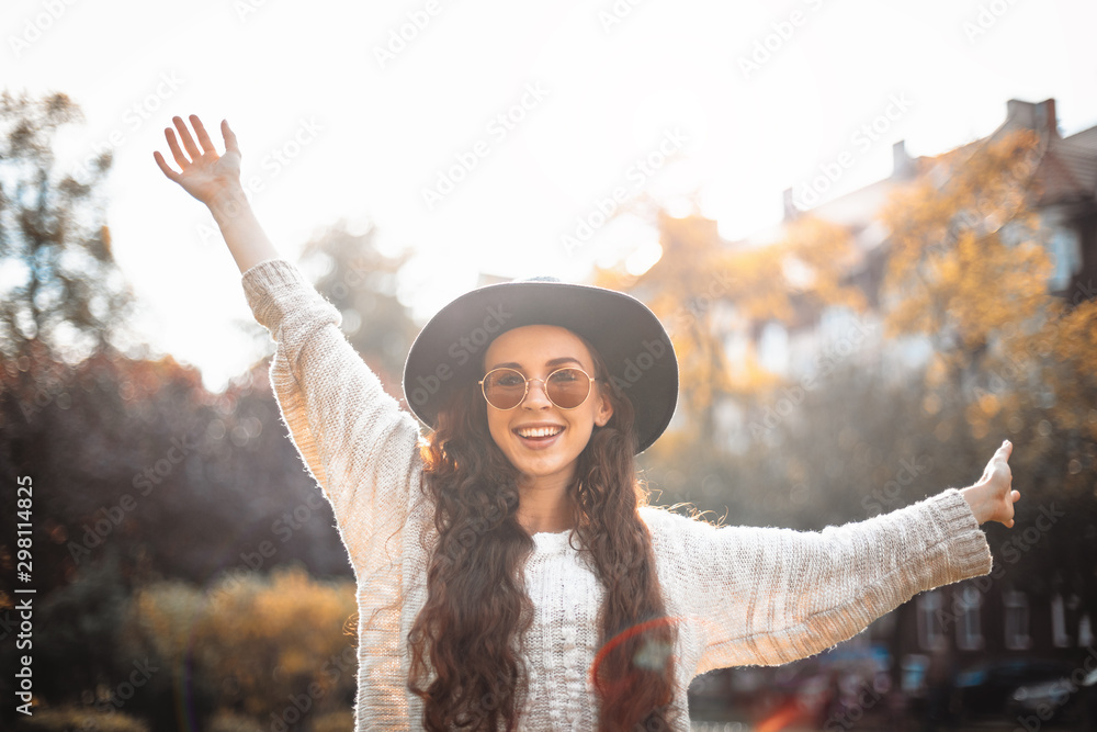Fototapety, obrazy: Happy stylish woman jumping with raising arms in autumn sunny day