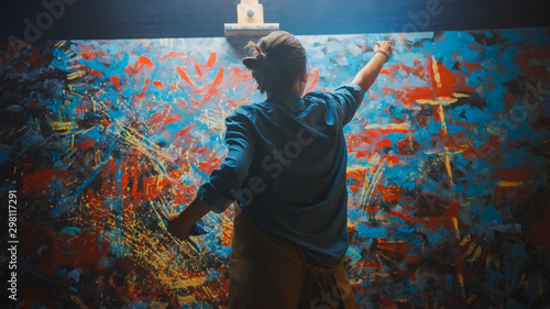 Obraz Talented Female Artist Works on Abstract Oil Painting, Using Paint Brush She Creates Modern Masterpiece. Dark and Messy Creative Studio where Large Canvas Stands on Easel Illuminated. - fototapety do salonu