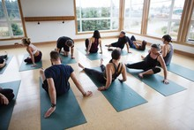 Yoga Class Sitting On Mats In ...