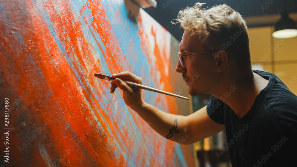 Fototapeta Portrait of Artist Working on Abstract Painting, Uses Paint Brush To Create Daringly Emotional Modern Picture. Dark Creative Studio Large Canvas Stands on Easel Illuminated. Side View Close-up Shot