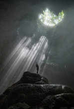 Girl Stands Under The Rays Of Light In A Deep Cave Jomblang Cave. Java, Indonesia