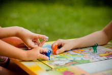 Family Playing A Board Game, One Kid Is On The Move And Capturing The Piece Of Another Player.Games In Kindergarden.Board Game And Kids Leisure Concept. Kids Holding Red People Figure In Hand. Blue