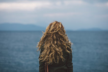 Curly Woman Shot From Behind Staring At The Sea