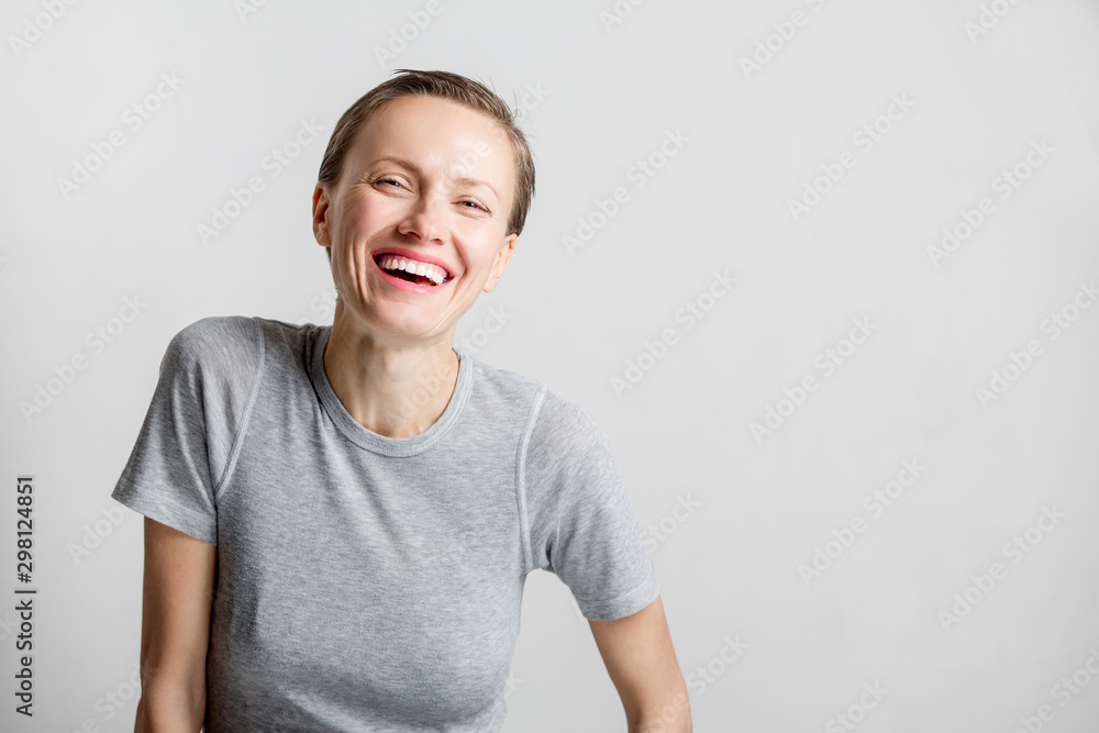 Fototapeta Happy cheerful young woman with short hair, natural makeup over light white grey background. Indoor portrait of beautiful brunette young woman