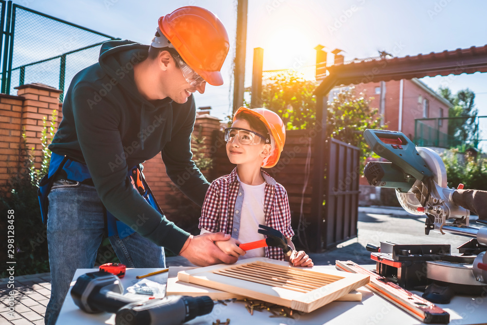 Fototapety, obrazy: The daddy teaching his little son to use hammer and nails