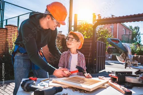 The daddy teaching his little son to use hammer and nails Tablou Canvas