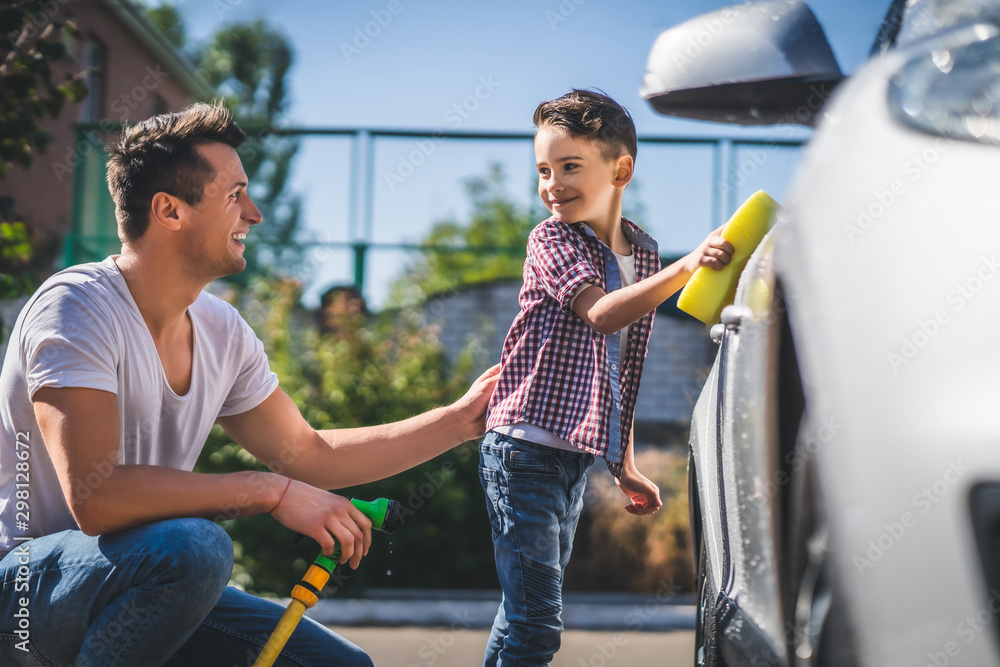 Fototapety, obrazy: The daddy and his son cleaning the car