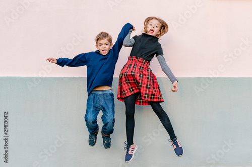 Photo Young girl with younger brother playing, jumping