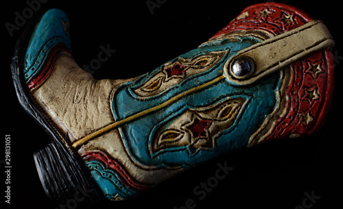 Fotografia, Obraz Sculpted red white and blue cowboy boot on side isolated on black background