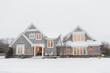 Leinwanddruck Bild - Wood shingled home in snow with warm lights illuminating windows