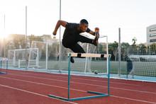 Black Man Jumping Hurdle On Stadium