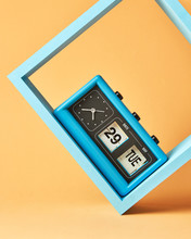 Retro Flipping Clock With Calendar On Wooden Blue Square Shelf On An Yellow Background With Copy Space.