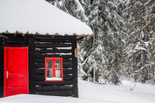Black Wooden House With Red Door And Window On Snow