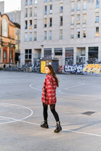 Beautiful, Cheeky Girl In A Plaid Shirt, Posing In The Sun Against The Background Of A Painted Wall