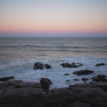 An Purple Sunset Meets The Water On A Rocky Coastline
