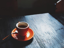 A Single Shot Of Espresso In An Orange Cup On A Wooden Table