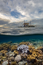 View Of Coral Reef And Boat In Sea Against Cloudy Sky