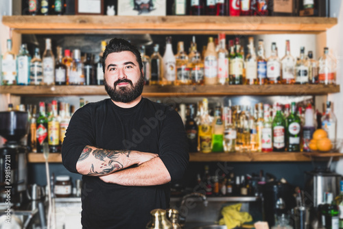 Photo Young hipster bartender with thick beard smiles at the counter with a background