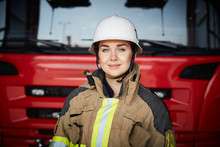 Portrait Of Female Firefighter Wearing Helmet Against Fire Engine At Fire Station