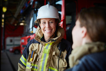 Smiling Female Firefighter Looking At Coworker In Fire Station
