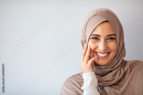 Poster Abou Dabi Young asian muslim woman in head scarf smile. Beautiful middle eastern woman wearing abaya. Arabian woman with happy smile. Strict formal outfit and elegant appearance. Islamic fashion.