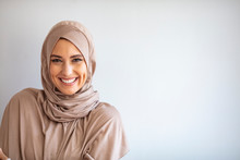 "Modern, Stylish And Happy Muslim Woman Wearing A Headscarf. Arab Saudi Emirates Woman Covered With Beige Scarf. ""Welcome"" Face. One Women Smile With White Background"