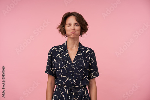 Photographie  Portrait of funny young woman with short brown hair puffing out cheeks and winki