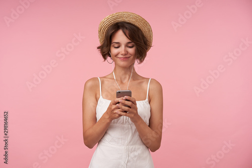 Pleasant looking brunette with casual hairstyle checking social networks with he Canvas Print