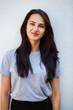 Leinwandbild Motiv Happy brunette woman in gray t-shirt