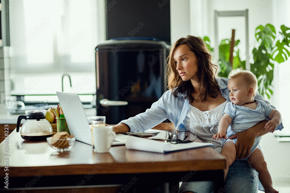 Fototapeta Young mother working on laptop while being with baby at home.