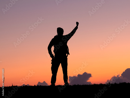 Canvas Prints Military Silhouette of travel man with backpack raised hands on the mountain. success concept.