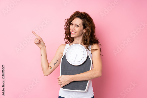 Fotografia  Young woman with curly hair holding a weighing machine over isolated pink backgr