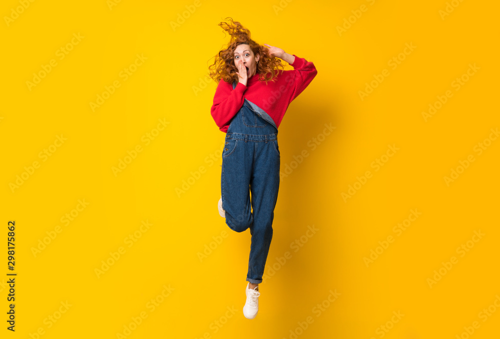 Fototapety, obrazy: Redhead woman with overalls jumping over isolated yellow wall