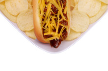 A Chili Cheese Hot Dog In Bun On White Plate With Potato Chips Isolated On White