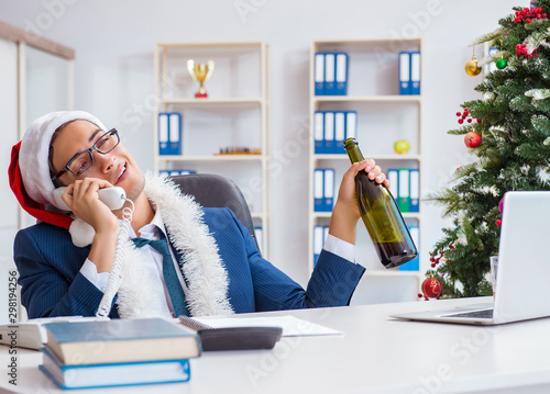 Fotografija  Businessman celebrating christmas holiday in the office