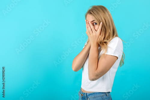 Scared pretty young woman hiding behind hands, peeping through fingers, curious Wallpaper Mural