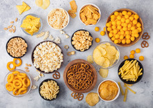 All Classic Potato Snacks With Peanuts, Popcorn And Onion Rings And Salted Pretzels In Bowl Plates On Light Background. Twirls With Sticks And Potato Chips And Crisps With Nachos And Cheese Balls.